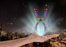 有应用象染色体的手在和与蓝色光 在被弄脏的城市前面在晚上 免版税图库摄影