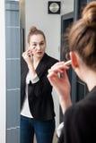 有应用concealer的衣服的常设美丽的年轻聪明的妇女 免版税图库摄影