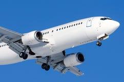 有底盘的乘客飞机在着陆前发布了在机场反对蓝天 免版税库存图片