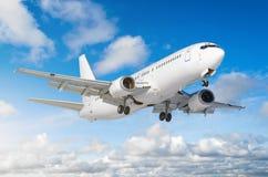 有底盘的乘客飞机在着陆前发布了在机场反对蓝天 库存照片