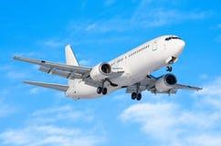 有底盘的乘客飞机在着陆前发布了在机场反对蓝天 免版税库存照片