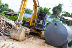 有废水治理坦克的中型挖掘机 库存图片