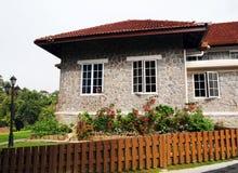 有庭院和篱芭的老石房子 库存照片
