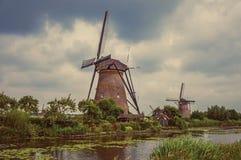 有庭院和运河的风车在小孩堤防的一多云天 免版税库存图片
