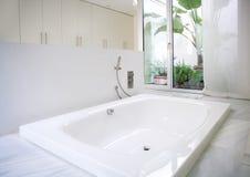 有庭院天窗的现代白色房子卫生间浴缸 免版税库存照片
