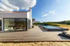 有庭院游泳池和木甲板的现代房子 图库摄影