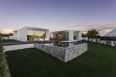 有庭院游泳池和木甲板的现代房子 免版税库存图片