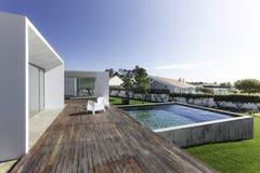 有庭院游泳池和木甲板的议院 免版税库存照片