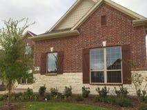 有庭院的一个新的砖和岩石房子 免版税库存照片