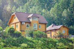有庭院的美丽的木房子在绿色森林,与自然一致的生态家附近 夏天好晴朗的天气 免版税库存图片