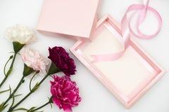 有康乃馨的桃红色礼物盒在白色 免版税库存照片