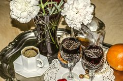 有康乃馨的水晶花瓶,无奶咖啡,与一个瓶的老水晶玻璃利口酒 免版税库存图片
