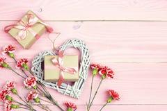 有康乃馨的礼物盒在桃红色木背景开花 复制空间 免版税库存照片