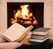 有开放书的手在壁炉附近 库存照片