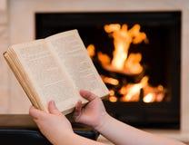 有开放书的手在壁炉附近 图库摄影