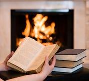 有开放书的手在壁炉附近 免版税库存图片