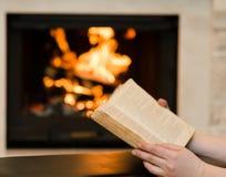 有开放书的手在壁炉附近 免版税图库摄影