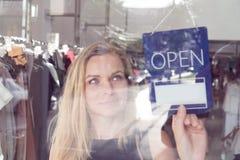 有开放和闭合的标志的商店工作者 免版税库存照片