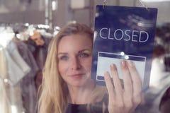 有开放和闭合的标志的商店工作者 免版税库存图片
