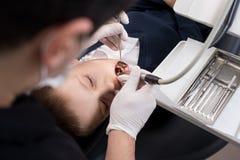 有开放嘴的男孩在小儿科牙医的钻治疗期间牙齿诊所的 库存图片