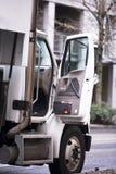 有开放小室门的半卡车在城市街道上 免版税库存照片