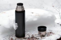 有开放杯子的热水瓶在雪 库存图片