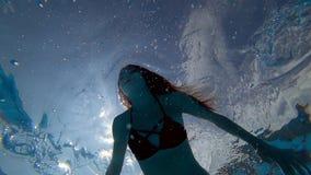 有开放眼睛的美丽的女孩漂浮在水面下在背景泡影的清楚的蓝色游泳池 股票录像