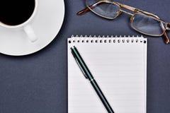 有开放笔记薄、笔、镜片和咖啡杯的办公桌 库存照片