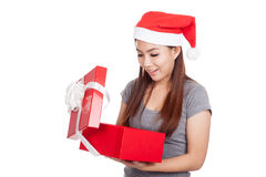 有开放红色圣诞老人的帽子的亚裔在礼物盒里面的女孩和神色 免版税库存照片