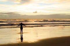 有开放胳膊的一名现出轮廓的妇女在一个海滩的海附近与太阳上升和反射在海水的阳光 免版税库存图片