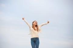 有开放胳膊的妇女在天空背景中在早晨 免版税库存照片