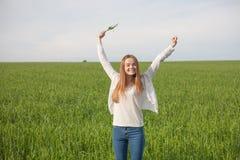 有开放胳膊的妇女在绿色麦田在早晨 库存图片
