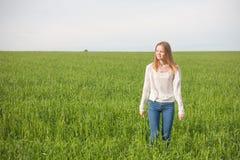 有开放胳膊的妇女在绿色麦田在早晨 免版税库存照片
