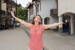 有开放胳膊的快乐的妇女在城市街道上 免版税库存照片