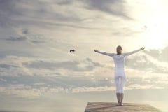 有开放胳膊的美丽的妇女思考在壮观的天空前面的 图库摄影