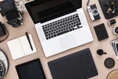 有开放膝上型计算机、片剂和葡萄酒照相机的设计师的书桌 在直接地之上 图库摄影