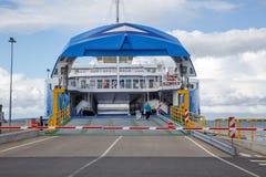有开放舷梯和空的准备好汽车的甲板的渡轮船上汽车和乘客 免版税图库摄影