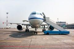 有开放行李舱的乘客飞机和搭乘ramp近在机场围裙 免版税库存照片