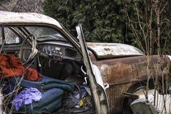 有开放里面的前门的被放弃的老生锈的汽车和肮脏的衣裳 库存图片