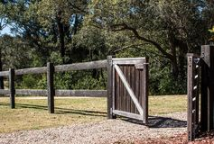 有开放门的木农村篱芭在与树的阳光下在背景中 库存照片