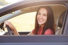 有开朗的笑的愉快的深色的女性司机,推进汽车,愉快接受它作为礼物从丈夫,享用好路d 免版税库存图片