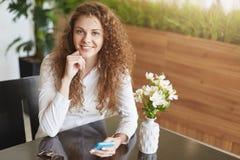 有开朗的笑,举行手机的, surfes社会网络或看法照片愉快的美丽的满意的少妇, connceted对hig 免版税库存图片
