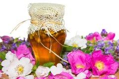 有开花和草本的蜂蜜瓶子 免版税库存图片