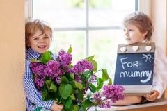 有开花的淡紫色花的两个可爱的矮小的兄弟姐妹男孩 免版税库存图片