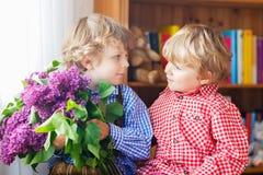 有开花的淡紫色花的两个可爱的矮小的兄弟姐妹男孩 免版税图库摄影