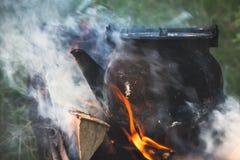 有开水的茶壶在篝火站立 库存照片