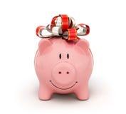 有弓和丝带的逗人喜爱的存钱罐 免版税图库摄影