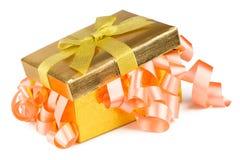 有弓和桃红色丝带的金黄配件箱 库存照片