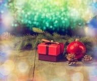 有弓圣诞树玻璃玩具的,杉木锥体,在老木桌上的杉木分支红色箱子 复制空间 免版税库存照片