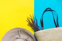 有弓柳条手织的海滩袋子的草帽与在明亮的黄色薄菏蓝色duotone背景的淡紫色枝杈 旅行假期 免版税库存图片